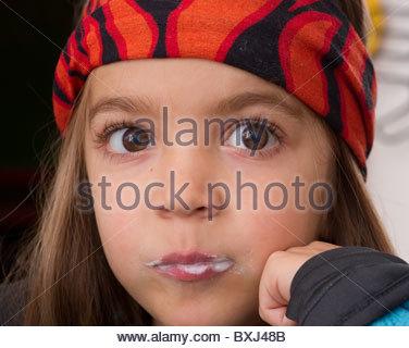 CHILD CHILDREN LITTLE BOY EATING YOGURT FOR BREAKFAST FACE PORTRAIT ALONE EYE CONTACT CLOSE UP BROWN EYES LONG HAIR - Stockfoto