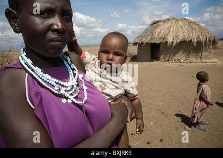 A maasai woman holds a baby outside her house in rural northern Tanzania, East Africa. - Stock Photo