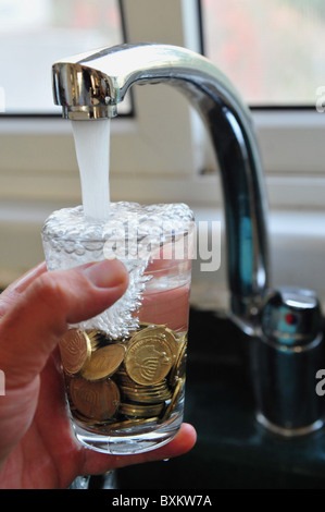 Conceptual photo of a tap filling glass full of gold coins with water illustrating wasting water and the high cost - Stockfoto