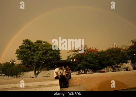 A couple sits in a public square under a rainbow using an umbrella as it rains in Yucatan state, Mexico, June 30, - Stock Photo