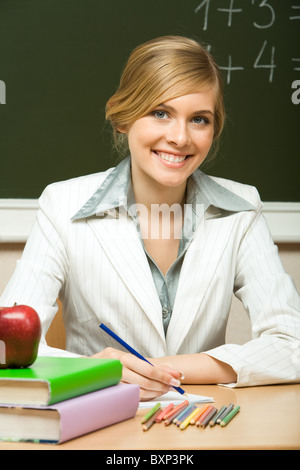 Portrait of young teacher checking copybook with books near by and looking at camera with smile - Stock Photo