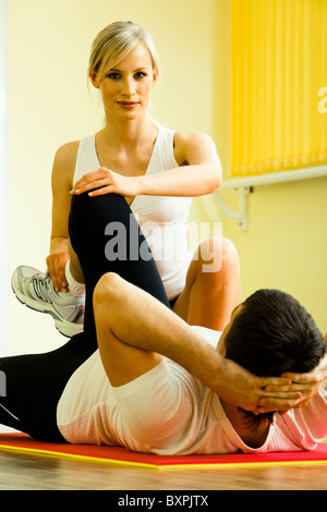 Image of young fitness instructor touching man's leg while he doing physical exercises - Stockfoto