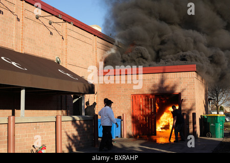 Restaurant workers try to contain a fire that started in the garbage area of the Granite City Food and Brewery in - Stock Photo