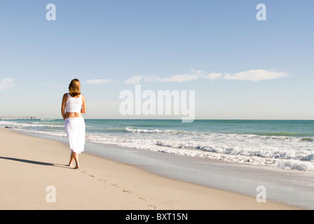 pregnant woman walking on beach - Stockfoto
