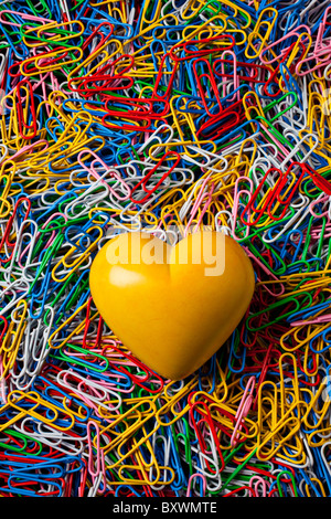 Yellow stone heart on paperclips - Stock Photo