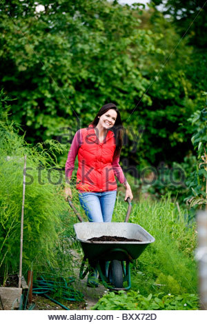 A young woman pushing a wheelbarrow on an allotment - Stock Photo