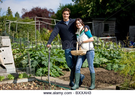 A young couple working together on an allotment - Stock Photo