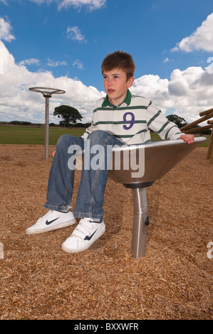 A MODEL RELEASED picture of an eleven year old boy in a play park in the Uk - Stock Photo