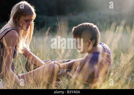 A young couple sitting in the grass, mans hand on the womans knee - Stock Photo