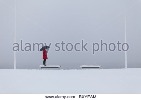 Solitary figure of a young woman wearing a red coat holding an umbrella standing on a bench in the snow - Stockfoto