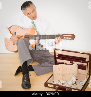 Businessman playing guitar in office - Stock Photo