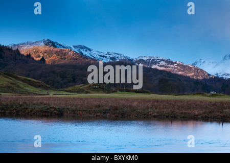 The rising sun lights up the snow topped fells at Elterwater in the Great Langdale Valley, Lake district - Stock Photo