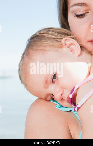 Mother with baby daughter hugging - Stock Photo