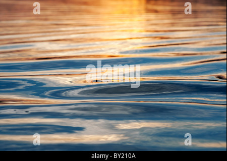 Abstract Golden water ripples at sunset on a lake in India - Stock Photo