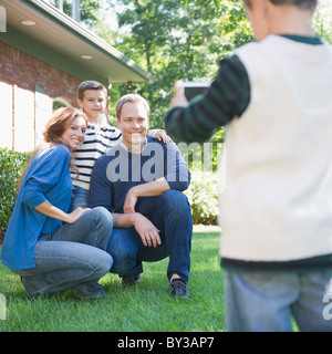 USA, New York, Flanders, Boy (4-5) taking photograph of mother, father and brother (8-9) - Stock Photo