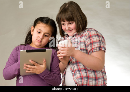 Two young friends playing electronic games on a touch pad screen - Stock Photo