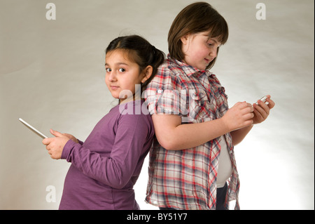 Two young girls playing games on touch pad screens - Stock Photo