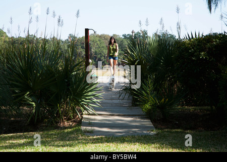 A woman and her dog walking down a wooden walkway - Stock Photo