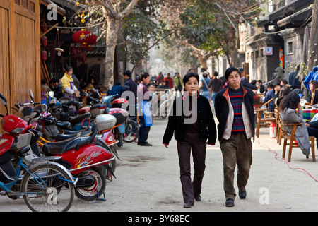 Two middle aged Chinese people strolling through the Hutong, Chengdu, Sichuan Province, China. JMH4411 - Stock Photo