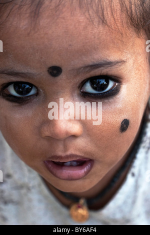 Small Indian child with kohl applied in spots to ward off 'the evil eye', South India. Kohl is an ancient eye cosmetic. - Stock Photo