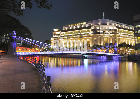 The Fullerton Hotel and the Cavenagh Bridge aglow in festive lights. - Stock Photo