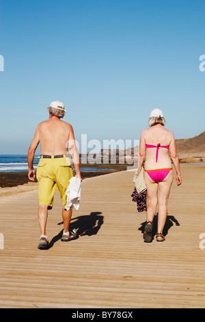 Elderly couple walking on wooden boardwalk near coast in Spain - Stock Photo