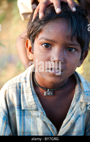 Young poor lower caste Indian street boy with a pierced nose. Andhra Pradesh, India - Stock Photo