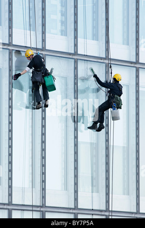 Two window cleaners hanging on ropes, cleaning the windows of the BBC Scotland offices, Pacific Quay, Glasgow, Scotland, - Stock Photo