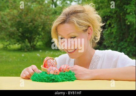 Young woman and painted Easter eggs on table – Easter decoration - Stockfoto