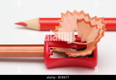 With a red pencil-sharpener and shavings. - Stock Photo