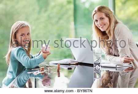 Mother watching daughter count coins from piggy bank - Stock Photo