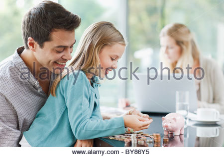 Father watching daughter count coins - Stock Photo