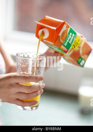 Girl pouring fresh orange juice - Stock Photo