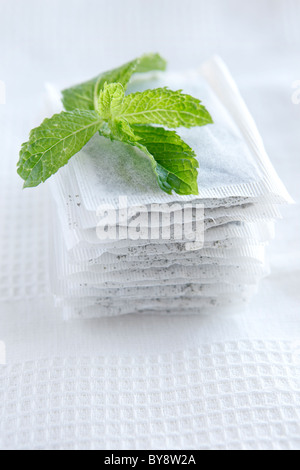 Mint leaves on mint tea bags on white tea towel - Stock Photo