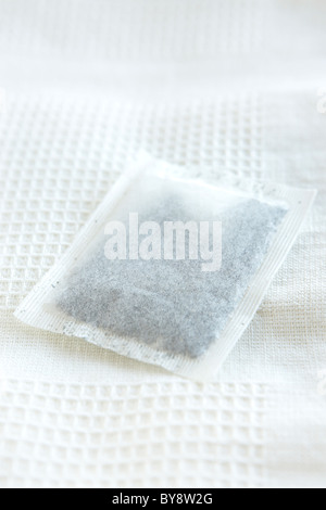 Mint tea bag on white tea towel - Stock Photo