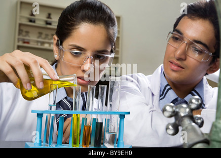 Girl pouring a liquid into a test tube - Stock Photo