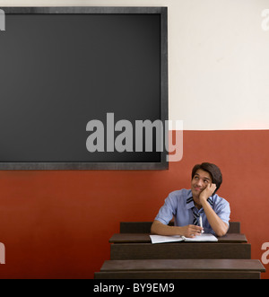 Boy daydreaming in a classroom - Stock Photo