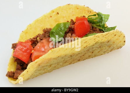 A taco shell and minced beef filling isolated over a plain background. - Stock Photo