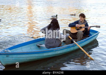 Man playing guitar in row boat - Stockfoto