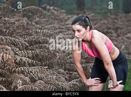Female taking a breather from a run in the forest - Stock Photo