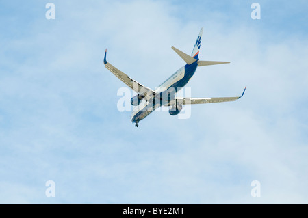 low flying commercial airliner plane planes airplane airplanes airport landing approaching landing take off taking - Stock Photo