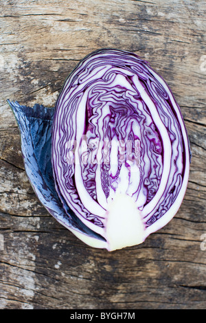 Overhead view of half of red cabbage on wooden table - Stock Photo