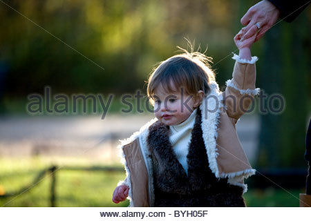 A baby girl holding her mother's hand in the park - Stockfoto
