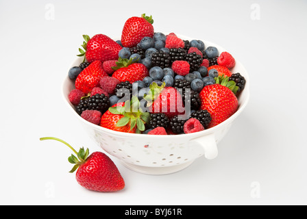 Agriculture - Fresh strawberries, red raspberries, blackberries and blueberries in a colander on a white surface. - Stock Photo