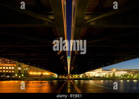 USA, Minnesota, Minneapolis, View underneath bridge across Mississippi River with city skyline at dusk - Stock Photo