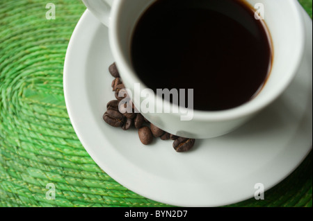 Cup of coffee on raffia mat with local freshly processed coffee beans on the side. Honduras, Central America. - Stock Photo