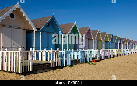 Colourful row of pastel coloured beach huts on beach - blue sky background - Stock Photo