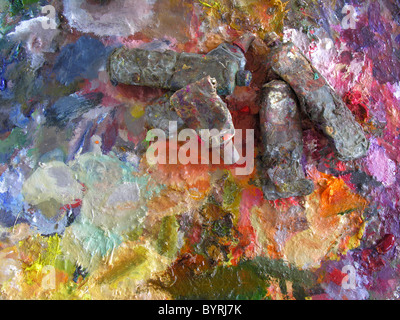 Artist palette with used oil-paint tubes - Stock Photo