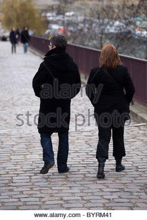 River Seine Paris France - couple walking across a bridge - Stock Photo