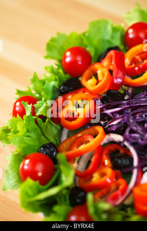 Macro photograph of fresh lettuce tomato pepper olive red onion and cabbage salad - Stock Photo
